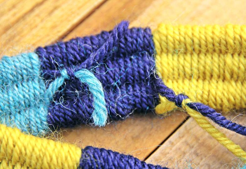 Wenn nur noch die Hälfte der Strohhalme herausschaut, diese etwas aus dem Gewebe herausziehen und weiter weben. Am Schluss das ganze Gewebe von den Halmen schieben. Für Farbwechsel neue Farben anknoten.