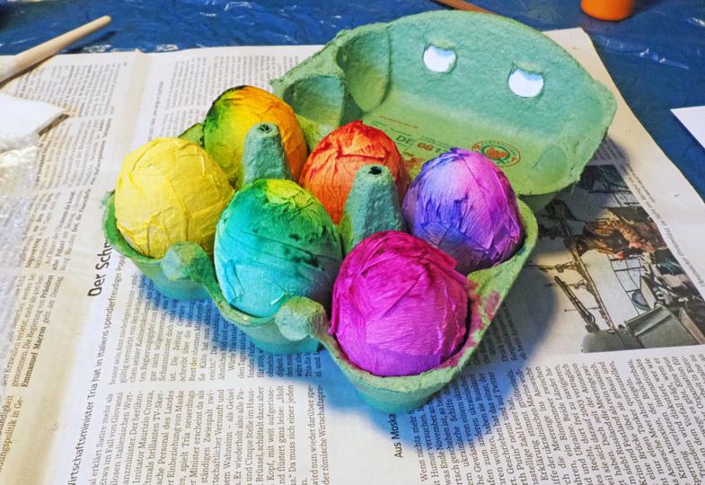 Die Papierstreifen anfeuchten und um die Eier wickeln. Diese dann in einem Eierkarton antrocknen lassen.