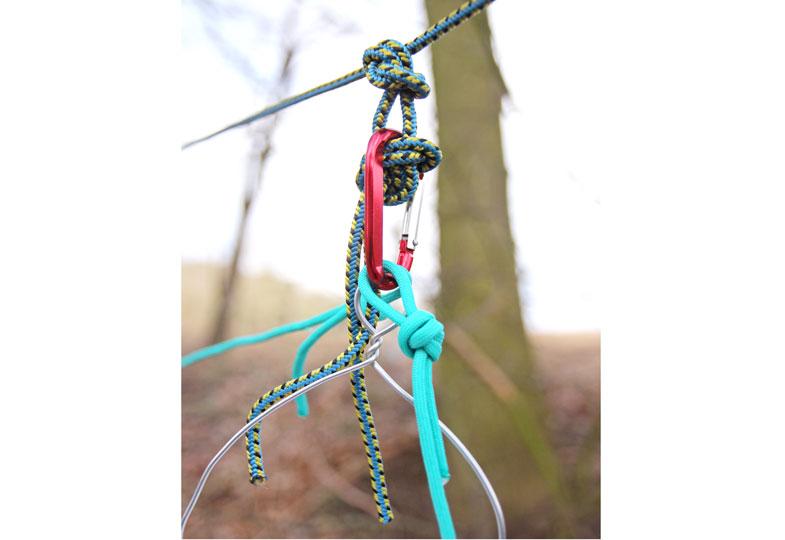 In den Knoten einen Karabiner hängen. Daran dann die übrigen zwei Seile befestigen.
