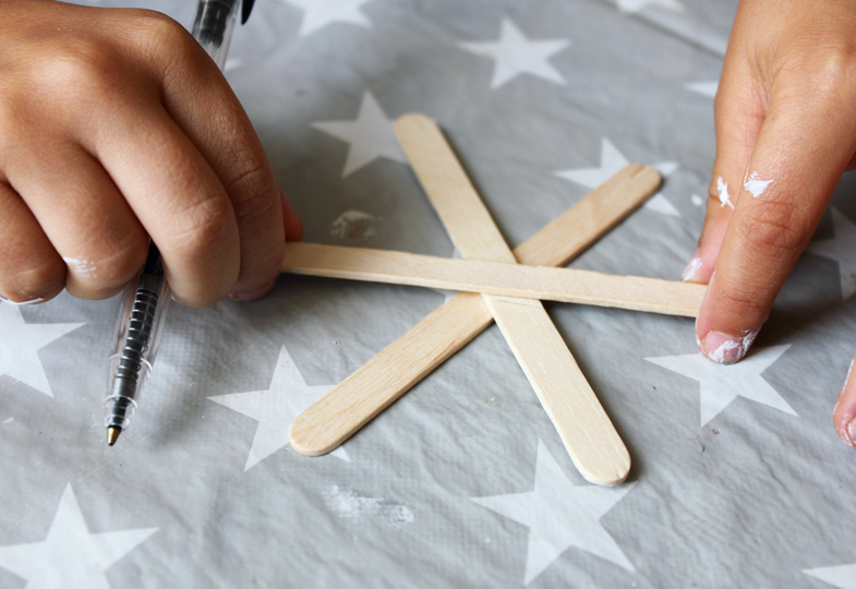 Holzstäbchen übereinander anordnen und die jeweilige Mitte markieren.