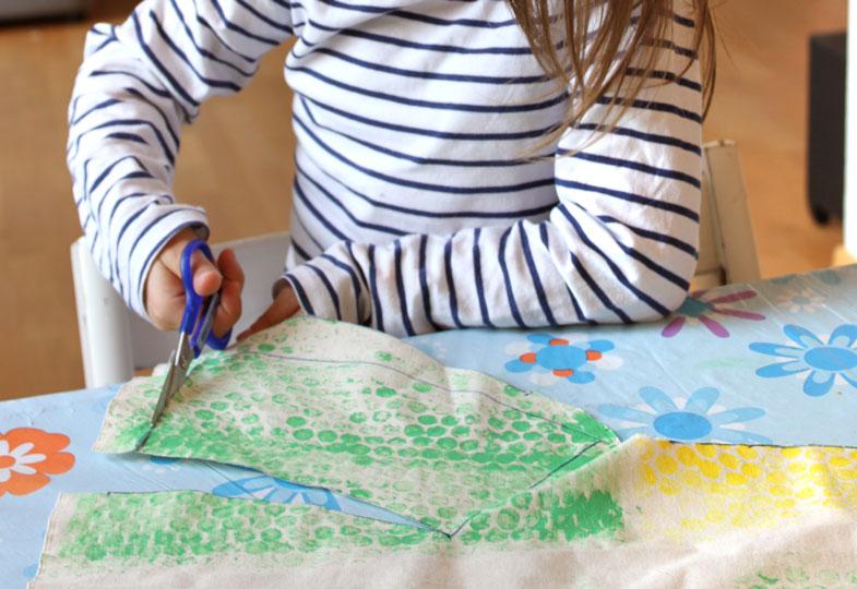 Becherschablone auf den Stoff auflegen, Muster aufzeichenen und dann ausschneiden.