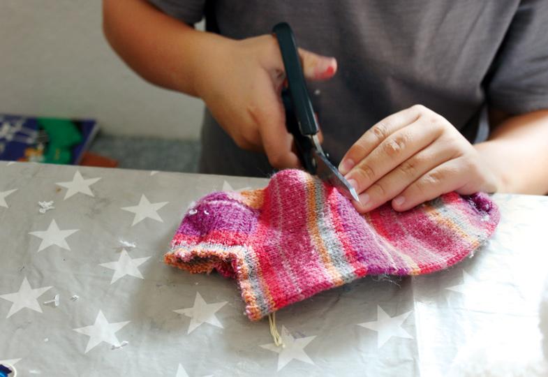 Eine bunte Socke zerschneiden, um daraus Mützen und Schals zu fertigen.
