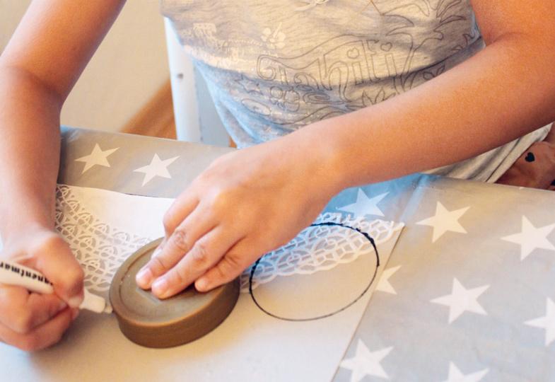 Tortenspitze an den Rand des Tonpapiers kleben, dann mithilfe eines Deckels Kreise auf das Papier zeichnen.