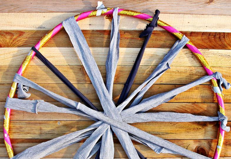 Aus dem Garn acht Schlaufen knoten und strahlenförmig um den Hula-Hoop legen.