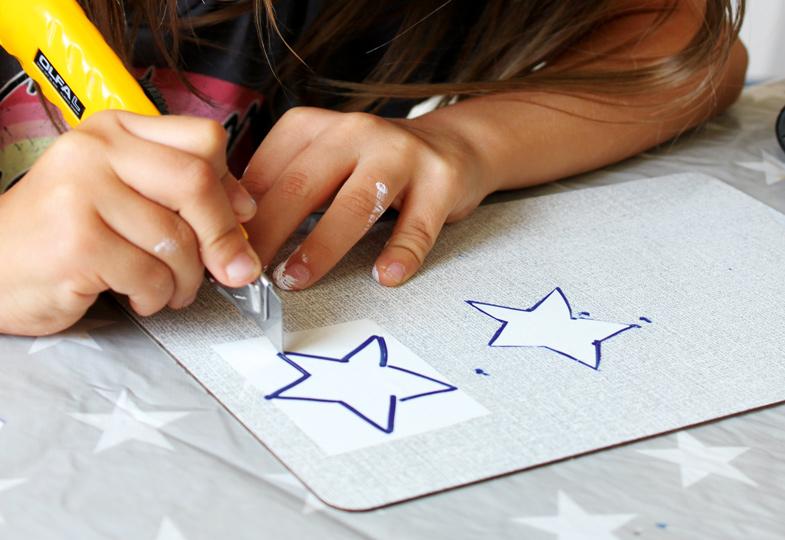 Klebeband auf ein Brettchen kleben, dann Sterne darauf malen und mit einem Cutter ausschneiden.