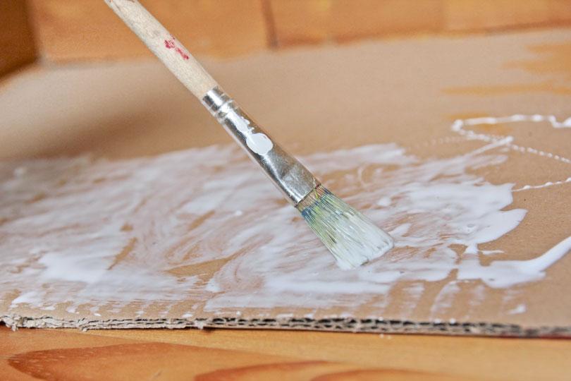 Für sandigen Boden Flüssigkleber auf dem Karton verteilen.