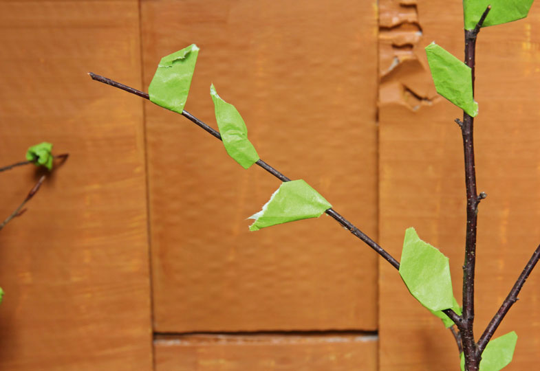 Für die Bäume Zweige in Astscheiben mit Loch stecken und grünes Papier daran kleben.