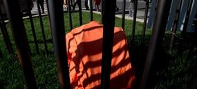 Ein Gefängnisanzug, so wie er in amerikanischen Gefängnissen getragen wird, liegt hinter Gittern als Teil einer Kunstinstallation gegen die Todesstrafe am 5. April 2017 in Washington. Menschen laufen daran vorbei.