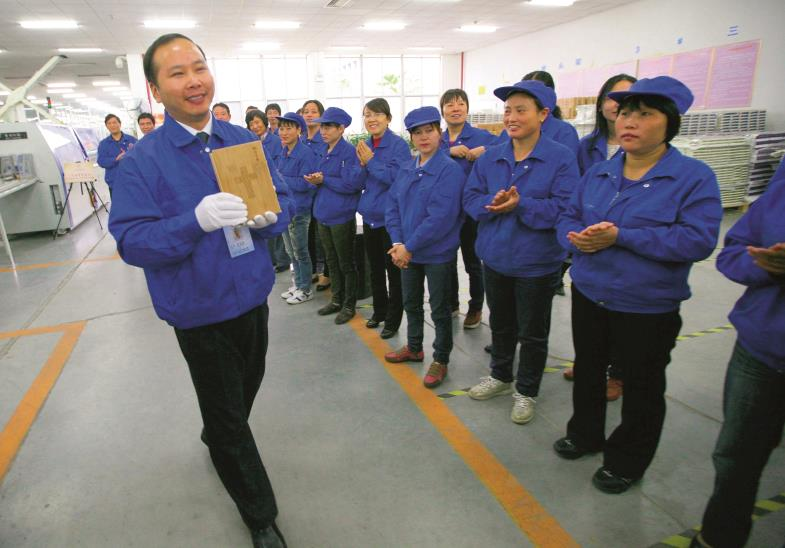 """Mit Stolz zeigt ein Arbeiter der """"Amity""""-Druckerei im chinesischen Nanjing die hundertmillionste Bibel, die im November 2012 dort hergestellt wurde."""