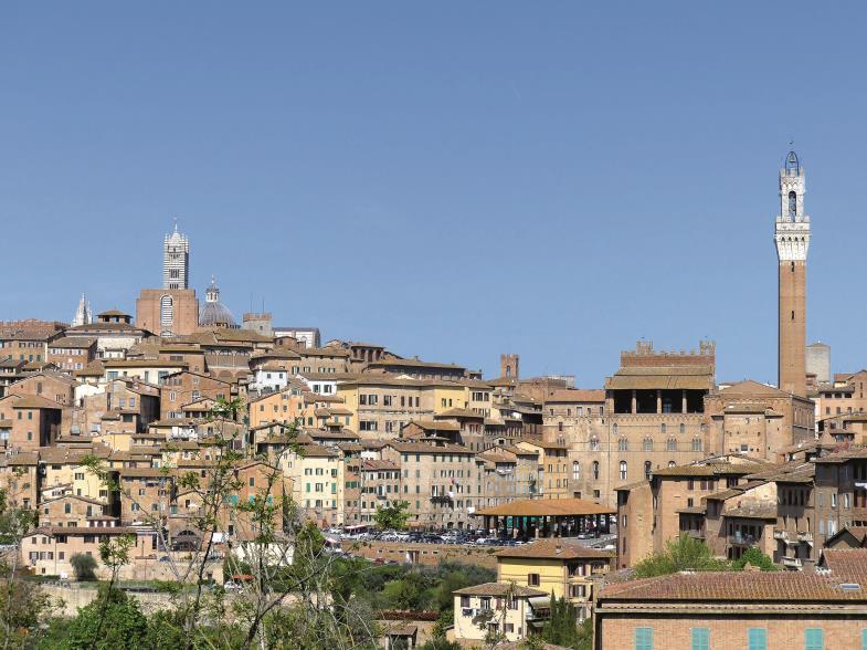 In prachtvoller Panoramalage auf drei Hügeln: Siena, von Südosten gesehen. Aus der Silhouette ragen der Dom (links) und der Rathausturm (rechts) heraus.
