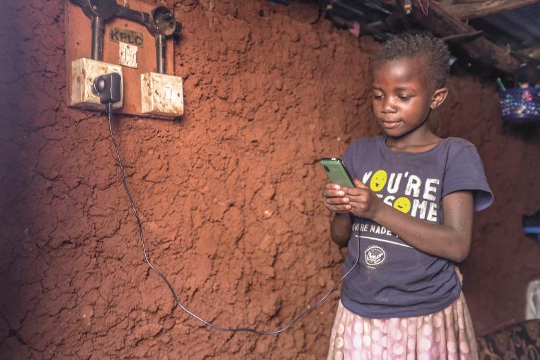 Die neunjährige Ann überprüft im Kibera-Slum von Nairobi, ob das Handy ihrer Mutter geladen ist. Stromausfälle sind häufig, Stromanschlüsse noch selten.