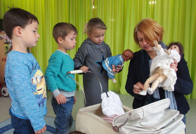 Gemeinsam mit ihrer Mutter stellt Emma die Puppen ihrer Oma vor