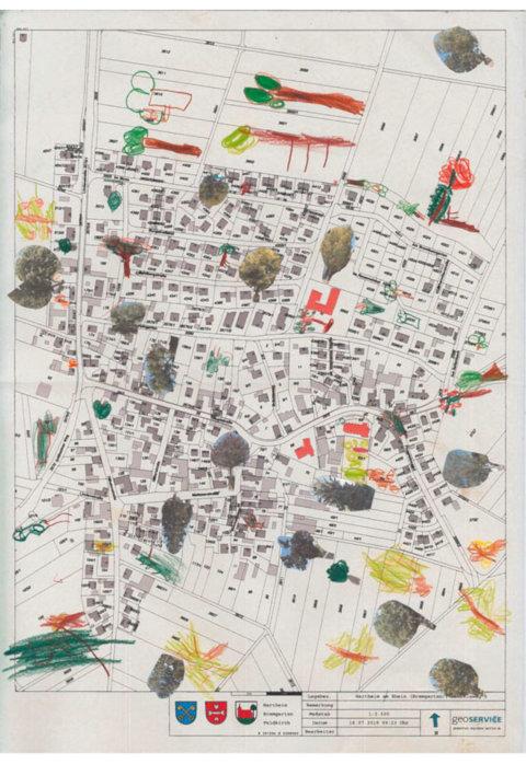 Auf der Flurkarte sind Straßen, Grundstücke und öffentliche Gebäude markiert. Die Kinder zeichnen und kleben die von ihnen gefundenen Bäume darauf