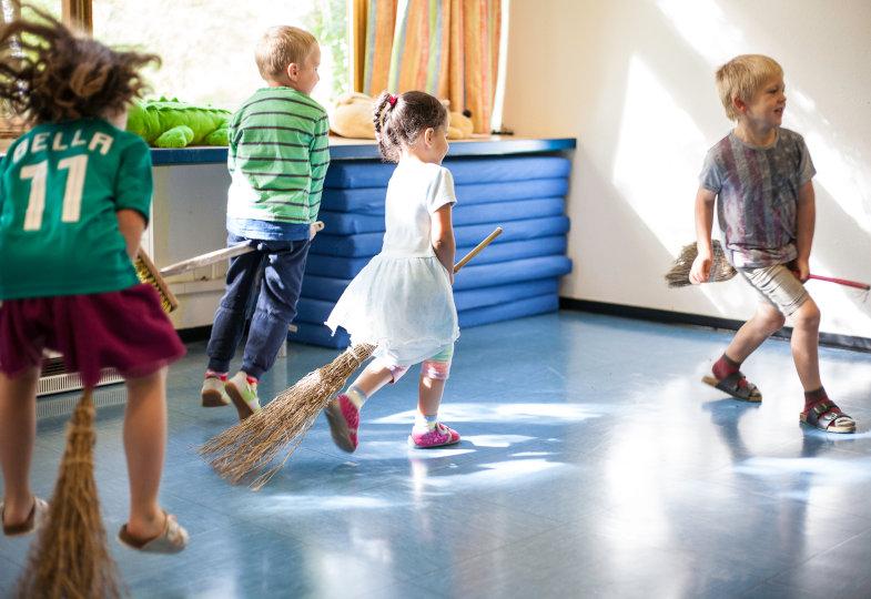 Wilde Feger: Mit teils selbst gestalteten Hexenbesen tanzen die Kinder durch den Raum
