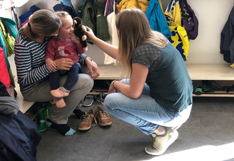 Die pädagogische Fachkraft begrüßt das Kind sowie seine Mutter auf Augenhöhe und nutzt den Kuschelaffen zur Kontaktaufnahme