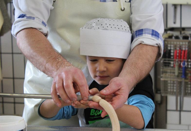 An der Füllmaschine machen die Kinder mit Unterstützung der Metzgers eigene Wurst