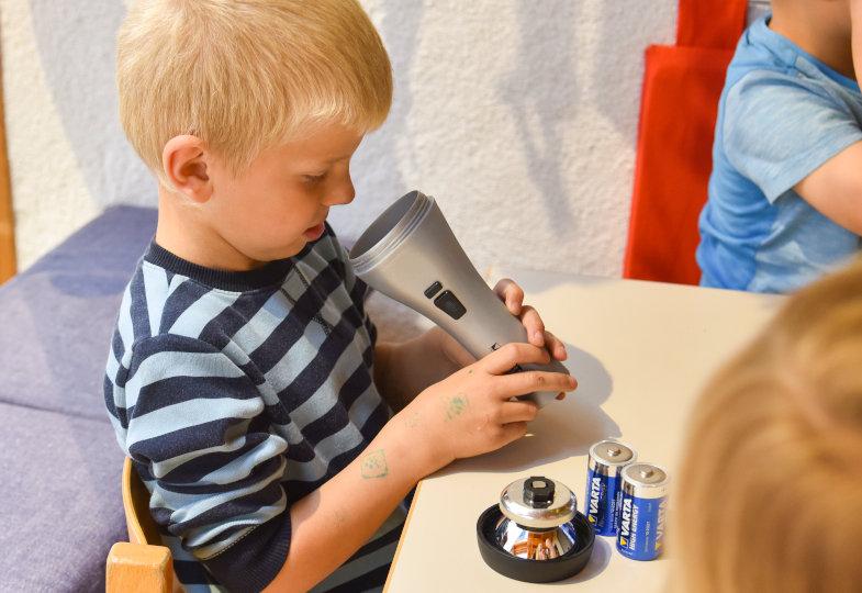Wie funktioniert eine Taschenlampe? Die Kinder bauen sie auseinander und finden Antworten