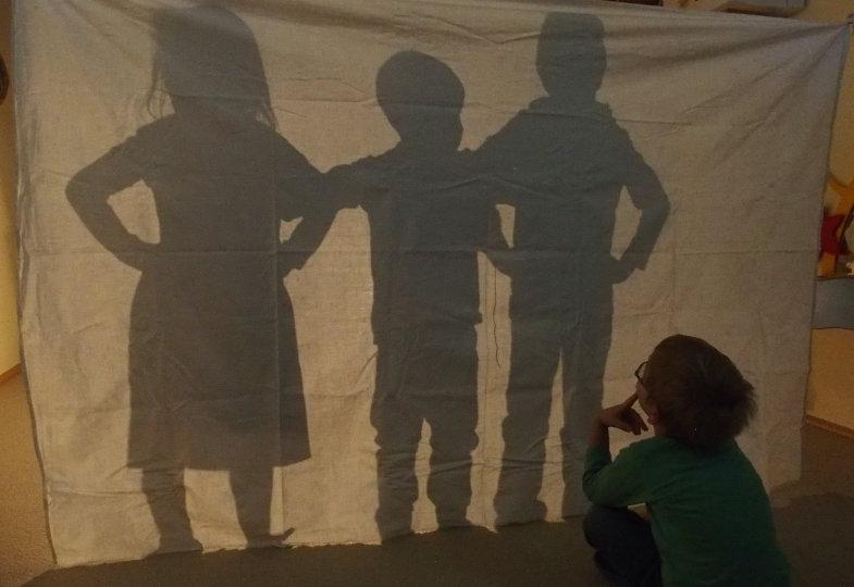 Wer versteckt sich hinter dem Tuch? Die Kinder testen, ob sie sich nur anhand ihrer Schatten erkennen