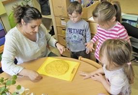 Die pädagogische Fachkraft schneidet die erkaltete Mămăligă mit einem Faden