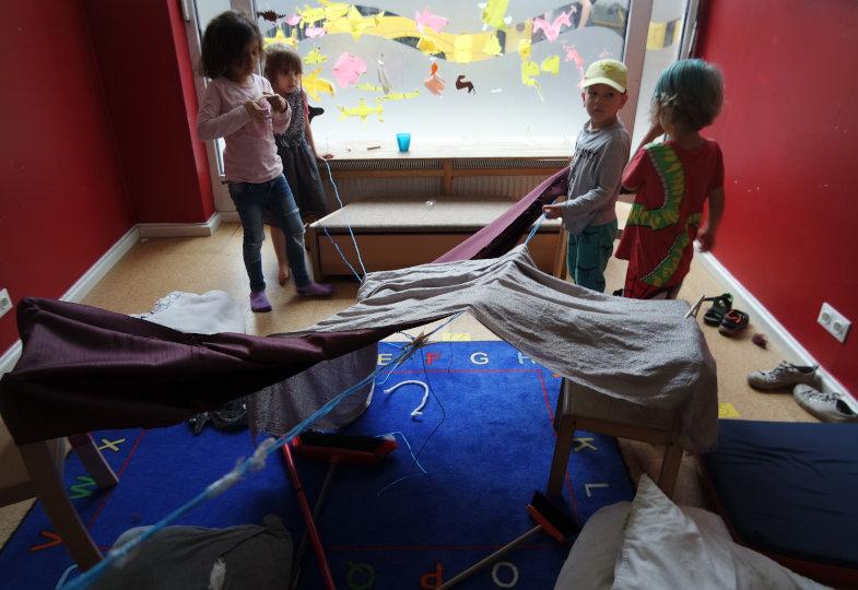 Wie bauen wir aus einer Stoffbahn ein Haus? Über gespannten Schnüren und Stühlen drapieren die Kinder den Stoff