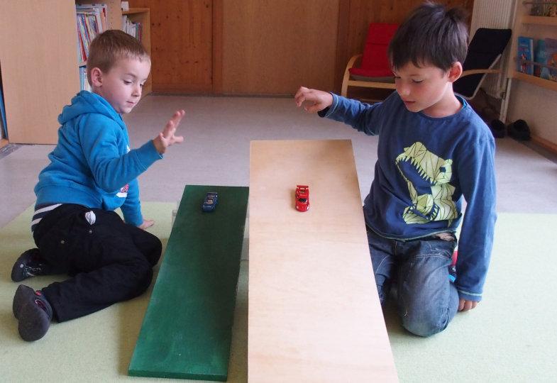 Wie kommen Spielzeugautos ins Rollen? Die Kinder experimentieren mit schiefen Ebenen