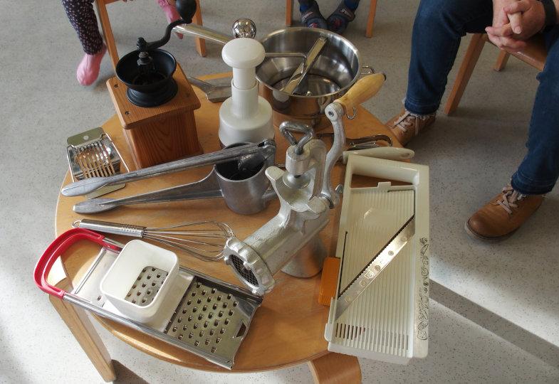 Eierschneider, Hobel und Co.: Die Kinder sammeln auf einem Tisch Küchenarbeitsgeräte