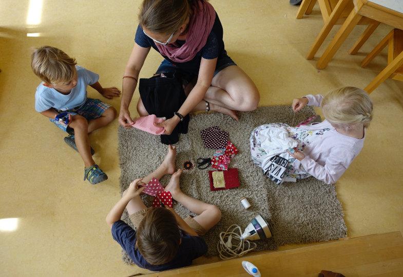 Statt wegwerfen: Die Erzieherin testet mit den Kindern, wie sich Kleidungsstücke flicken lassen