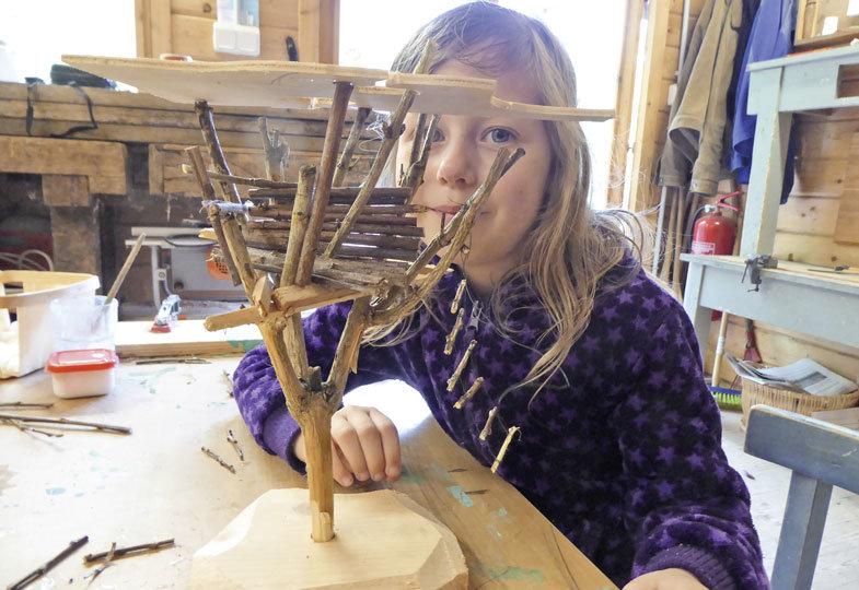 Ein Dach sägt Clara aus Sperrholz aus und befestigt es mit Leim an den Zweigen.