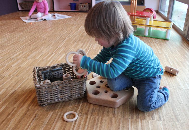 Mit Fotos versehene Körbe unterstützen Kleinkinder dabei, das Spielmaterial nach Gebrauch wieder aufzuräumen