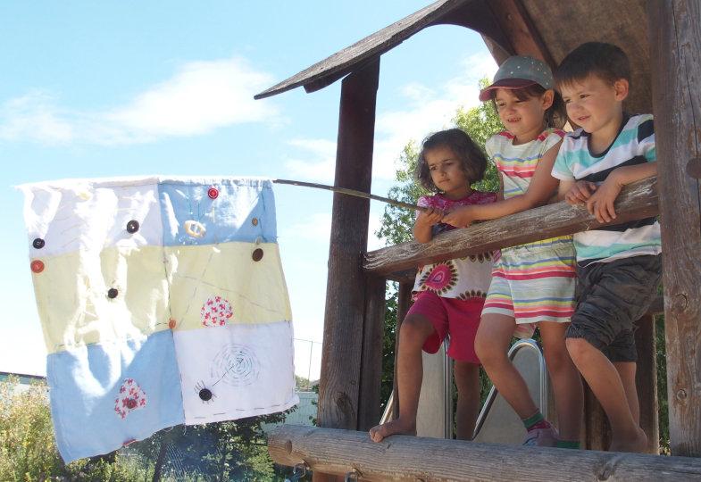 Die Kinder hissen ihre selbst genähte Fahne im Außengelände