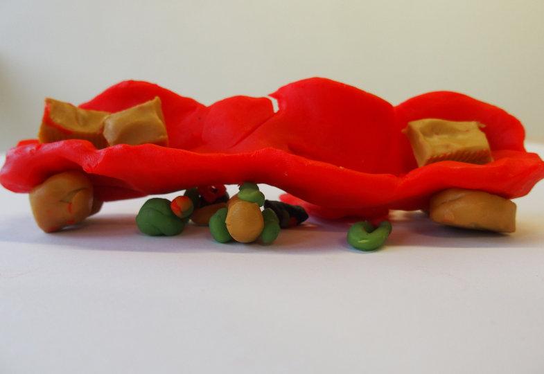 Ein knallrotes Sofa, darunter: Bälle, Äpfel und ein Donut