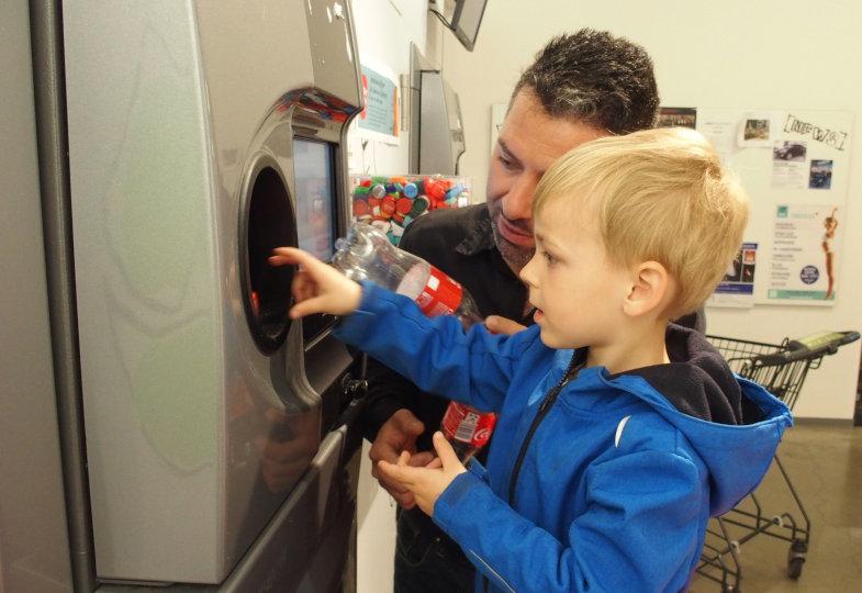 Der Filialleiter zeigt den Kindern, wie sie die Flaschen korrekt einwerfen und wo sich der Sensor für die Kisten befindet