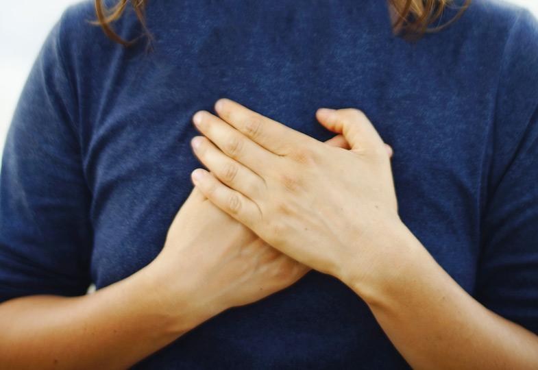 Die Hände an die Brustmitte halten