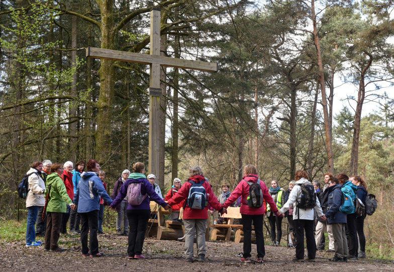 Auf einem Rastplatz steht eine Pilgergruppe betend um ein großes Holzkreuz herum.