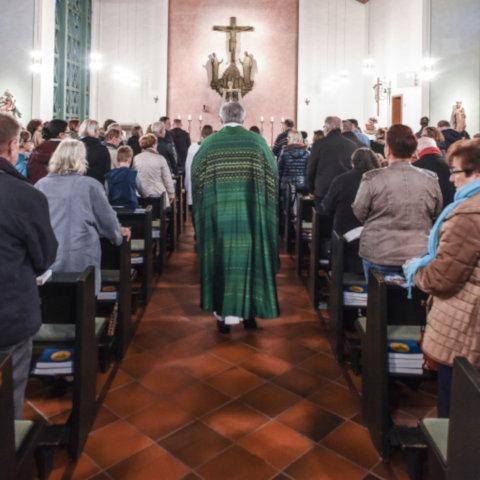 Priester und liturgische Dienste ziehen durch die versammelte Gemeinde zum Altar.