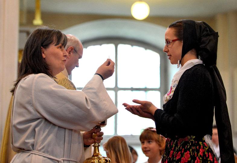 Eine Kommunionhelferin übt ihren Dienst während des Fronleichnamsgottesdienstes in der sorbischen Lausitz (Sachsen) aus.