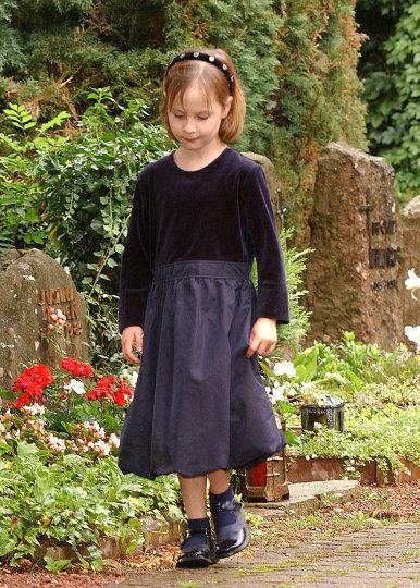 Ein Kind läuft auf einem Friedhof.
