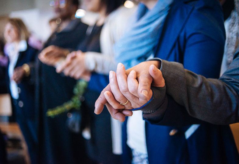Betende fassen einander an den Händen