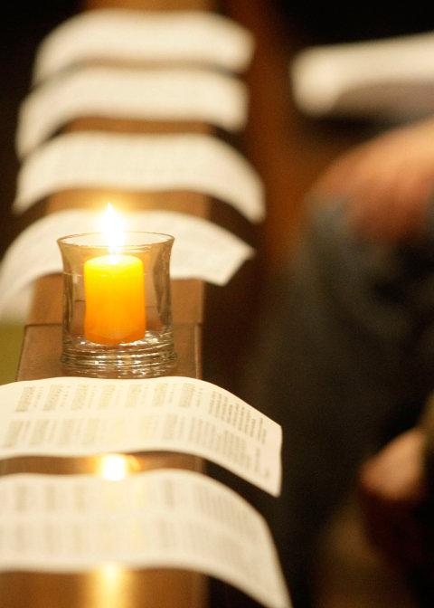Brennende Kerzen auf einer Kirchenbank