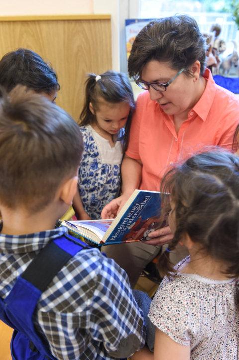 Kinder stehen um eine Erzieherin, die aus einer Kinderbibel vorliest.