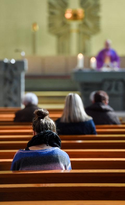Menschen in Kirchenbänken