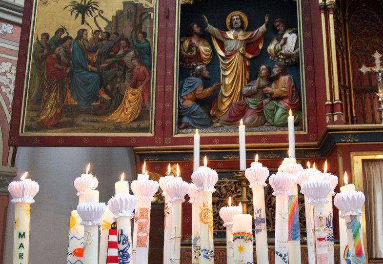 Erstkommunionkerzen brennen vor einem Bild des auferstehenden Christus