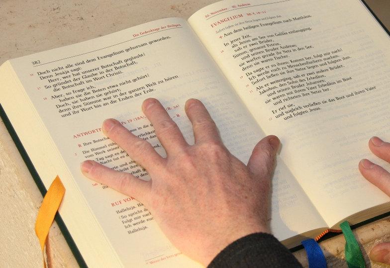 Hände streichen die Seiten eines Lektionars glatt.
