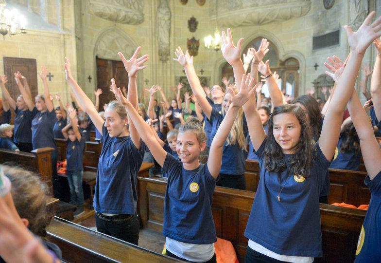 Kinder und Jugendliche heben beim Singen die Hände in die Höhe