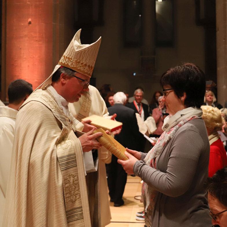 Bischof Stephan Ackermann überreicht einer Lektorin das neue Lektionar.