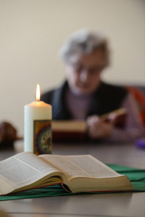 Eine aufgeschlagene Bibel und eine brennende Kerze auf einem Tisch, im Hintergrund liest eine Frau in einer Bibel