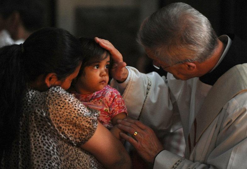 Ein Priester legt einem Kind die Hand auf