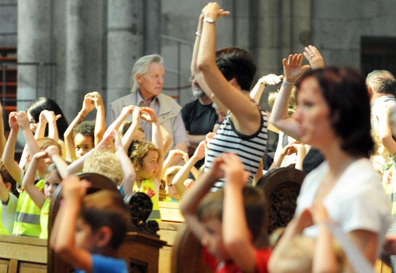 Kinder im Gottesdienst begwegen zu einem Lied ihre Arme