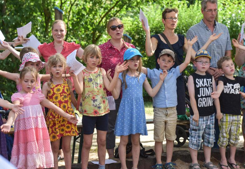 Kindergartenkinder und ihre Eltern feiern Gottesdienst am Sandkasten