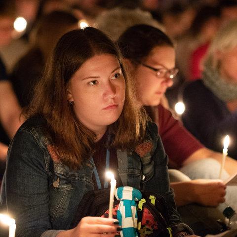 Jugendliche feiern mit Kerzen in den Händen Gottesdienst